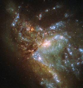 "This image, taken with the Wide Field Planetary Camera 2 on board the NASA/ESA Hubble Space Telescope, shows the galaxy NGC 6052, located around 230 million light-years away in the constellation of Hercules. It would be reasonable to think of this as a single abnormal galaxy, and it was originally classified as such. However, it is in fact a ""new"" galaxy in the process of forming. Two separate galaxies have been gradually drawn together, attracted by gravity, and have collided. We now see them merging into a single structure. As the merging process continues, individual stars are thrown out of their original orbits and placed onto entirely new paths, some very distant from the region of the collision itself. Since the stars produce the light we see, the ""galaxy"" now appears to have a highly chaotic shape. Eventually, this new galaxy will settle down into a stable shape, which may not resemble either of the two original galaxies."